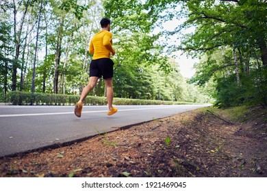 Back view of man running on park road