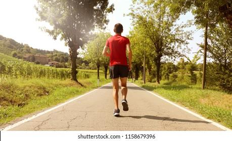 Back view man running outdoor