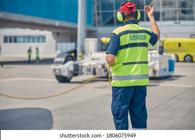 Back view of a man in a safety vest and headphones directing a vehicle operator