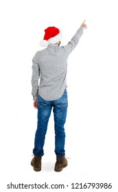 Back view of a man in a Santa Claus hat pointing upwards. Rear view people collection. backside view of person. Isolated on white background. Guy in New Year's clothes