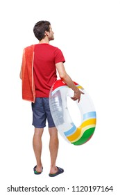 Back view of a man in shorts with an inflatable circle. The guy on the beach. Rear view people collection.  backside view of person. Isolated over white background. young guy looks around at the beac