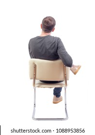 Back view of a man sitting on a chair. Rear view people collection.  backside view of person.  Isolated over white background. A guy in a gray jacket is working or studying. The guy sits cross leg