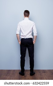 Back view of a man standing close to light blue wall, wearing formal wear and put his hands in the pockets