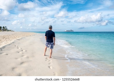 Back View of a Man Standing on a Caribbean Beach and Looking at a Cruise Ship on the Horizon
