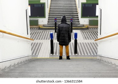 Back view of man standing on the stairs. Urban underground lonely passage. Single adult.Minimalism.Lines.Pesrspective