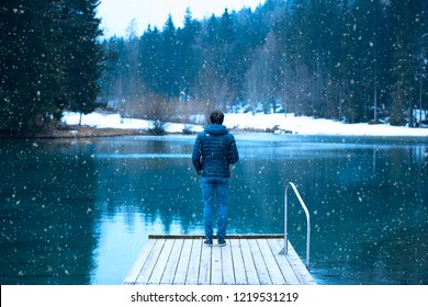 Back view of a man stands on wooden pier at cold winter seasonal lake during snowfall.