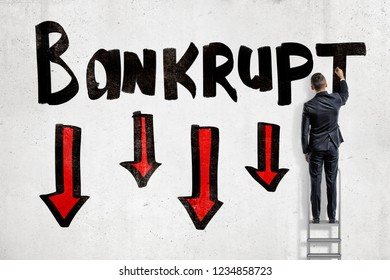 A back view of a man in suit standing on a ladder and writing 'Bankrupt' on a wall with four red arrows pointing down. Going bankrupt. Decreasing profits. Dangerous situation. Risk in businessses.