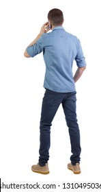 back view of a man talking on the phone. backside view of person.  Rear view people collection. Isolated over white background. A man in a shirt with his hand in his pocket talking on a smartphone.