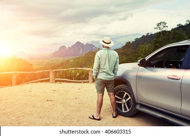 Back view of a man is thinking about this amazing world, while is standing on a mountain against jungle view. Young male traveler is enjoying beautiful landscape during road trip on suv in Thailand