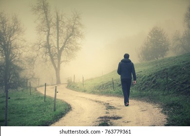 Back view of a man walks alone on misty countryside road with electric fence.
