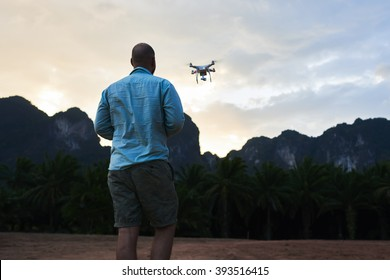 Back view of man wanderer is shooting video with radio controlled drone, against silhouette of rock mountains at sunset. Male web author is taking photos on flying quadcopter during trip in Asia