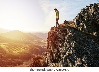 Back view of man wanderlust tours excited with natural environment and scenery during during colorful sunset. Hiker exploring nature in wild trip adventure