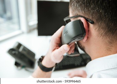 Back view of man in white shirt and eyeglasses which sitting by the table with computer and talking on phone. Close up view