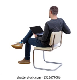 Back view of a man who sits on a chair with a laptop.  Rear view people collection.    Isolated over white background. Side view of a stylish guy who sits on an office chair with a laptop.