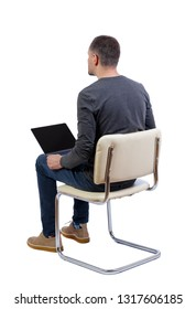 Back view of a man who sits on a chair with a laptop.  Rear view people collection.   Isolated over white background. A student in a gray jacket looking forward sitting on a chair with a laptop.