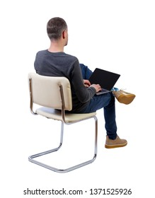 Back view of a man who sits on a chair with a laptop.  Rear view people collection.   Isolated over white background. A stylish guy with a laptop is sitting on a chair with his legs crossed.