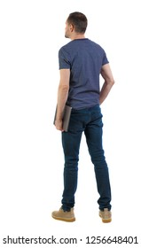 Back view of a man who is standing with a laptop. Rear view people collection.  backside view of person.  Isolated over white background. A student is thoughtfully holding a laptop in his hand