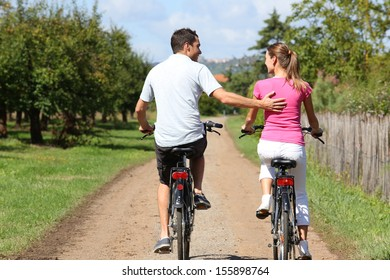 Back view of man and woman riding bicycles