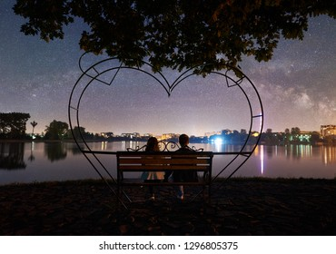 Back view of man and woman sitting on a bench on the shore near lake under tree. Couple enjoying beautiful view of evening sky full of stars, Milky way and luminous town on background. Outdoor concept