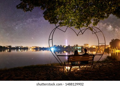 Back view of man and woman sitting on a bench near campfire on the shore near lake under tree. Couple enjoying amazing view of evening sky full of stars, quiet water surface, city lights on background