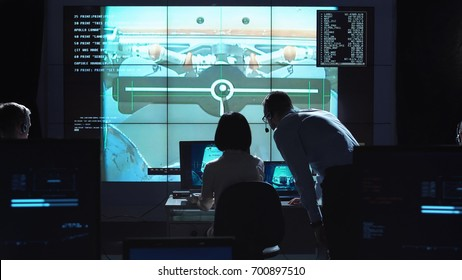 Back view of man and woman in space flight control center. Docking of space modules. Elements of this image furnished by NASA.