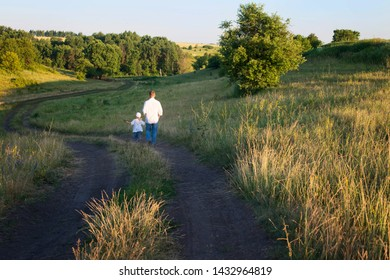 Back view of mature father and little girl daughter enjoy their walk in nature. Parenthood, fatherhood, adoption, family and people concept. Precious family moments outdoors.