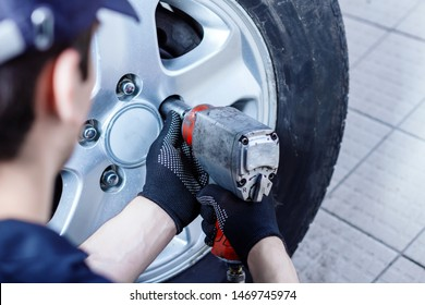 Back view of mechanic is repairing car at service station. Closeup repairman is removing wheel by electric wrench, tyre mounting equipment at workshop auto repair shop. Tire fitting concept.