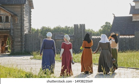 Back view of medieval women going on camera at wooden fortress background. Clothes of medieval woman of 14-15 century.