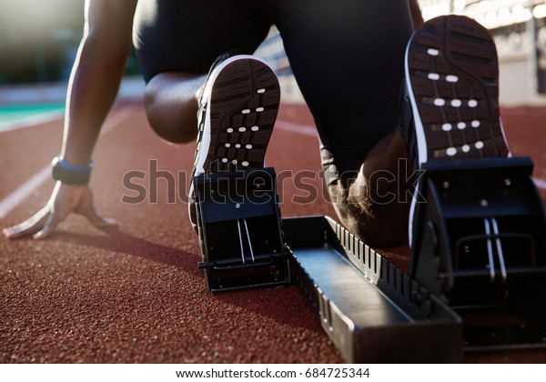 Back view of men's feet on starting block ready for a sprint start