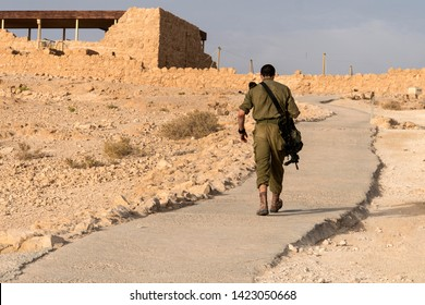Back view of a military going alone among deserted territory somewhere in the middle east. Masada fortification, Israel, war trainning. Tired soldier walking in desert after military mission. Conflict