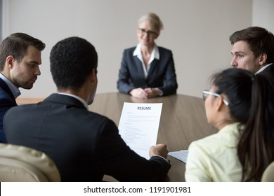 Back view of millennial HR managers read middle aged female applicant resume considering her candidature for open position, young employers discuss smiling woman candidate cv at interview