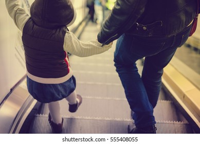 Back view of mother and child going together on escalator background. Shopping mall, airport travel, love care