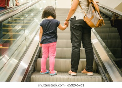 Back view of mother and child going together on escalator background.Shopping mall, airport travel, love care, protection concept.