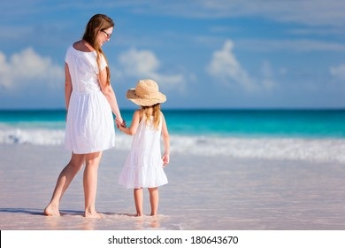 Back view of mother and daughter at Caribbean beach