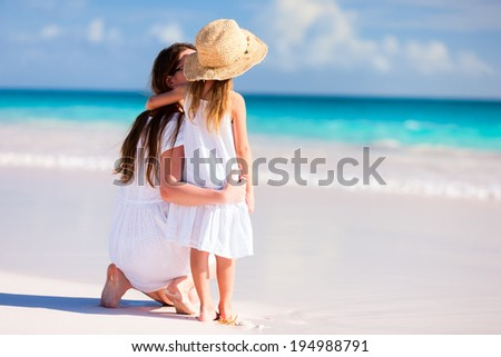 52e27a6b581e4 Back view of mother and daughter at Caribbean beach enjoying summer vacation