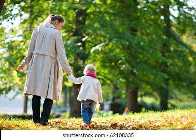 Back view of mother and daughter walking in beautiful autumn park
