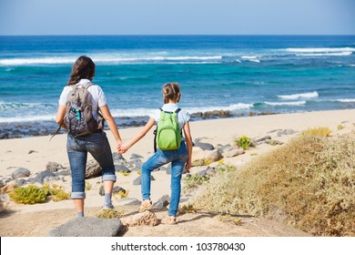 Back view of mother with her daughter walking on a beach, wearing jeans and white shirts