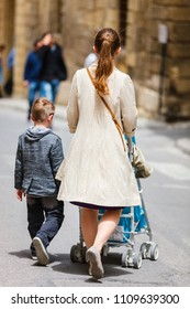 Back view of mother with her son and toddler daughter in stroller walking in city street in Malta Europe