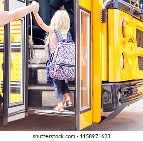 Back view of  mother holding her daughter by hands. Fist ride on school bus.
