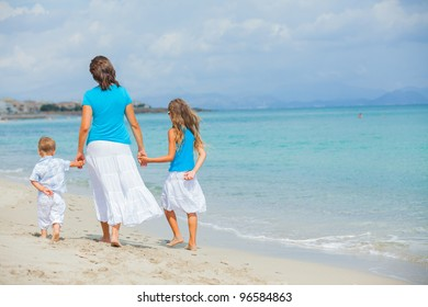Back view of mother and two kids having fun on tropical beach