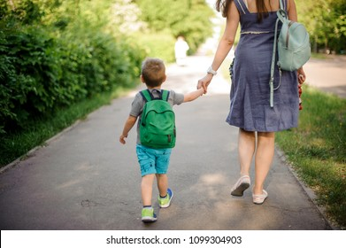 Back view of mother walking down the street with a little son with a backpack on sunny summer day