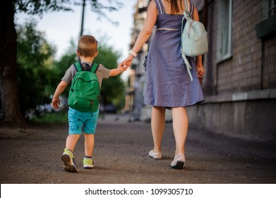 Back view of mother walking down the street with a little son with a backpack on summer day
