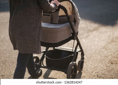 Back view of mother walking with her baby in stroller. Grey stroller outside, sunset
