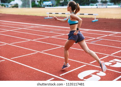 Back view of a motivated sportswoman running a distance at the stadium