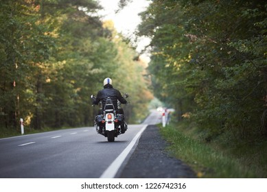 Back view of motorcyclist in black leather jacket and white helmet riding motorbike along hilly road between tall green trees on sunny summer day. Active lifestyle, love to adventures concept.