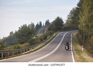 Back view of motorcyclist riding motorbike up twisted empty asphalt road on bright sunny summer day by green forest trees under clear blue cloudless sky.