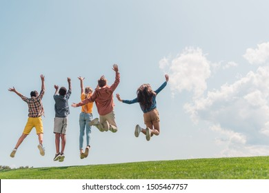 back view of multicultural kids jumping and gesturing against blue sky