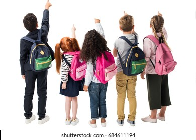 back view of multiethnic children with backpacks pointing at copy space isolated on white