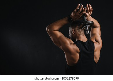 back view of muscular african american man training with dumbbell isolated on black