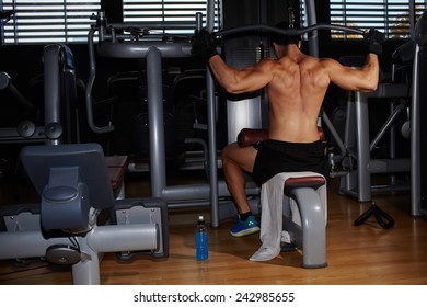 Back view of muscular build athlete exercising on pull down weight machine